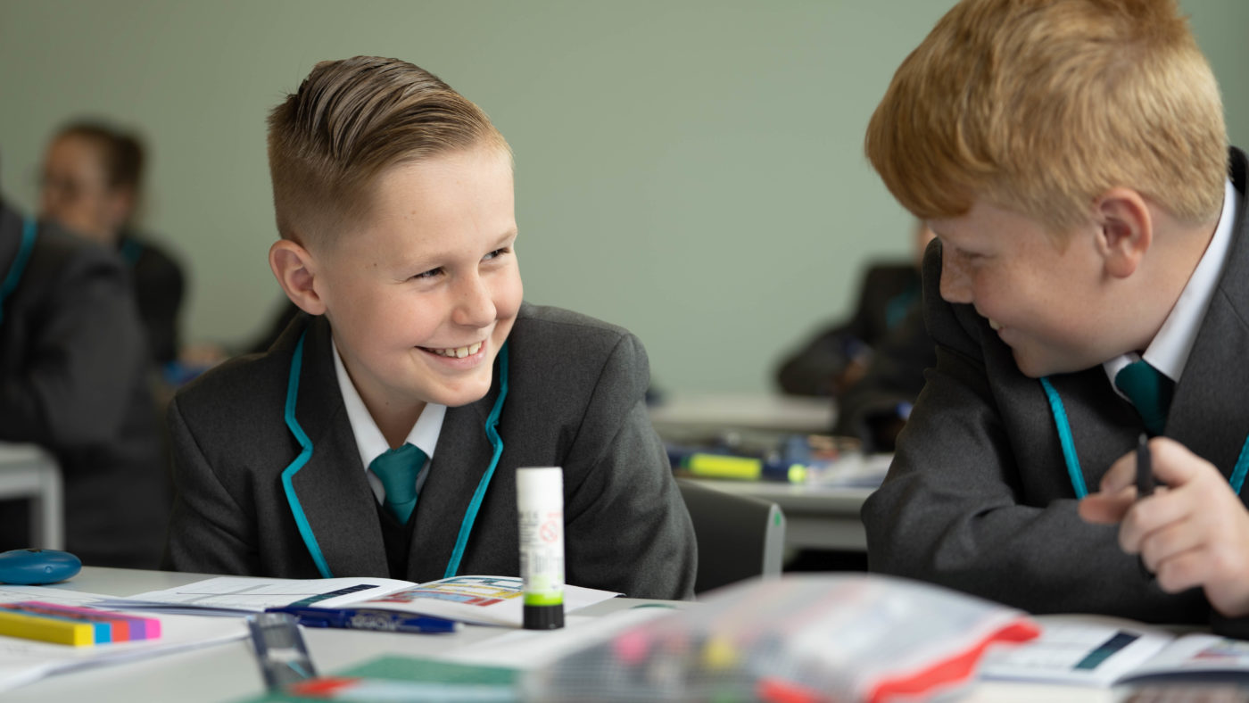 two year 7 school students at a desk smiling at each other